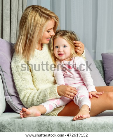 Mother and baby playing and smiling. Happy family at home interior.