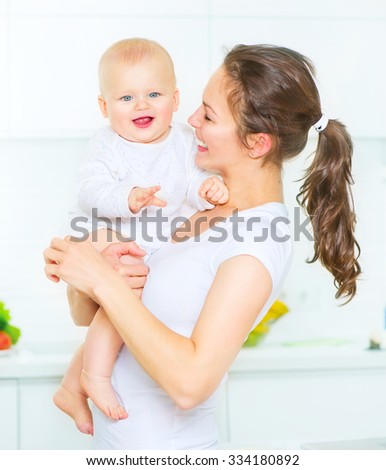 Mother and Baby playing and smiling together. Love. Happy cheerful family Mom and Baby girl kissing and hugging at home. Beautiful healthy mother and little daughter. Maternity concept. Parenthood - stock photo