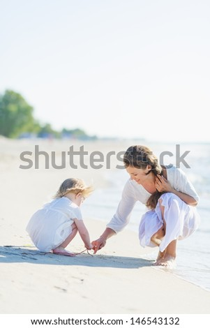 Mother and baby playing on beach - stock photo