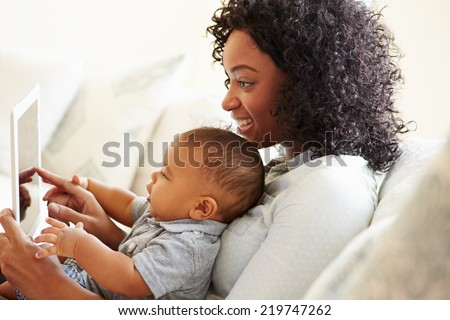 Mother And Baby Playing With Digital Tablet At Home - stock photo