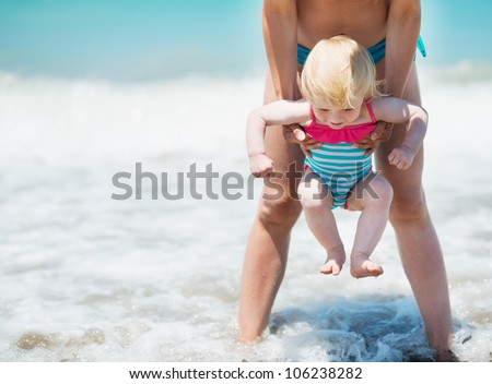 Mother and baby playing with sea waves - stock photo