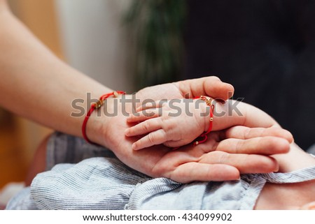 Mother and Baby's hand in closeup - stock photo