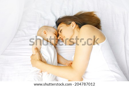 Mother and baby sleep in bed - stock photo