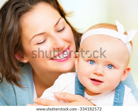 Mother and Baby smiling together. Love. Happy cheerful family Mom and Baby girl kissing and hugging at home. Beautiful healthy mother and little daughter. Maternity concept. Parenthood. Motherhood