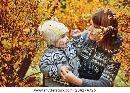 mother and baby son in fall having fun - stock photo