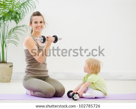 Mother and baby spending time doing fitness - stock photo
