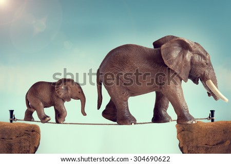mother and baby toy elephants walking on a tightrope subtle vintage filter and lens flare - stock photo