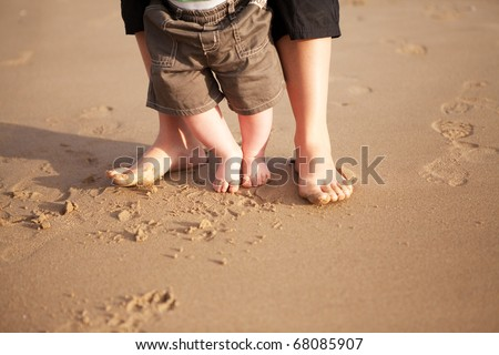 Mother and baby walking on beach sand - stock photo