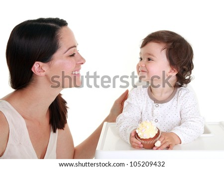 Mother and baby with cupcake in highchair - stock photo