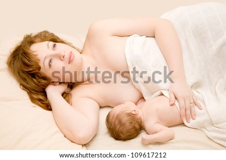 Mother and baby. Young redhead woman  breastfeeding newborn baby and dreaming about the future. They are lying on the bed hidden by a sheet. The symbol mother love and happiness - stock photo