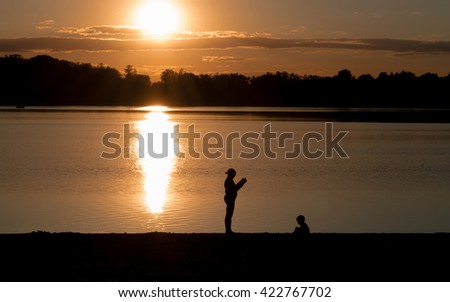 Mother and boy are having fun under sunset on a lake