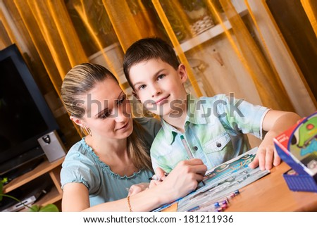 Mother and boy doing homework together and posing, looking at camera - stock photo