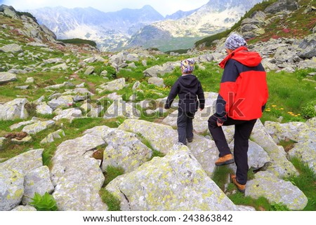 Mother and boy walking across large boulders on the mountain - stock photo