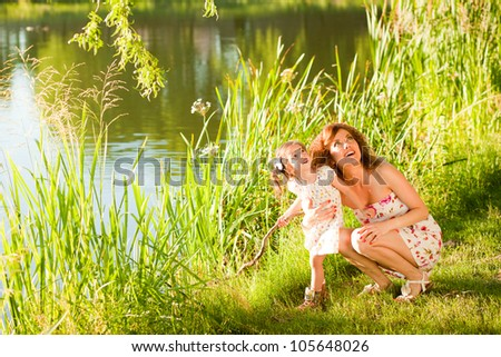 mother and child at the lake enjoying a sunny day - stock photo