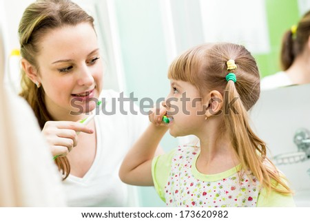 mother and child daughter brushing teeth in bathroom - stock photo