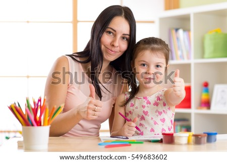 Mother and child daughter drawing together with pencils at table