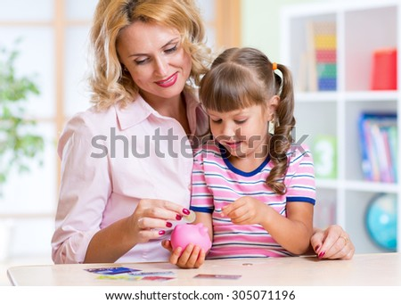 Mother and Child Daughter Putting Coins into Piggy Bank - stock photo