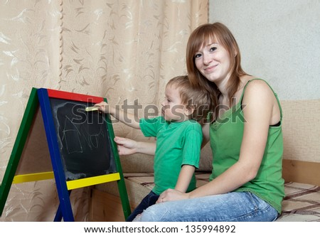 Mother and child draws on the blackboard with chalk