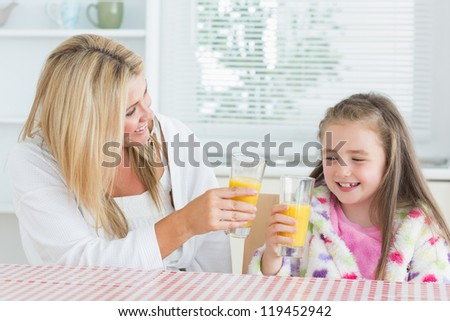 Mother and child drinking juice at the kitchen - stock photo