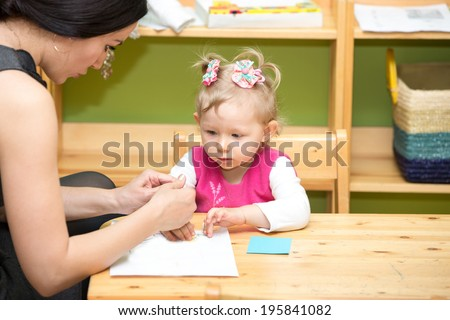 Mother and child girl drawing together with color pencils in preschool at the table in kindergarten - stock photo