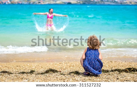 Mother and child having fun at the beach. Little girl is watching mother having fun in the sea. She is jumping and splashing water. - stock photo