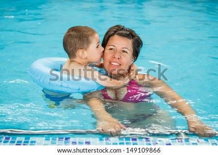 Mother and child in blue pool - stock photo