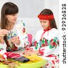 Mother and child in Ukrainian national cloth doing crafts - stock photo