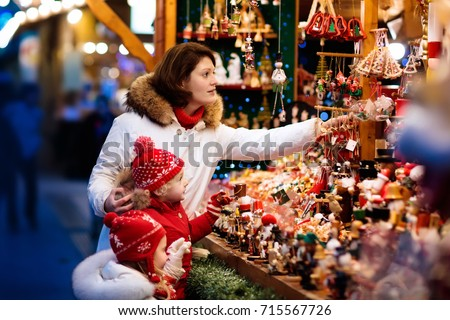 Mother and child in warm hat watching handmade glass Christmas tree ornaments at traditional German Xmas street market. Family with kids shopping for Christmas presents on winter fair on snowy day.