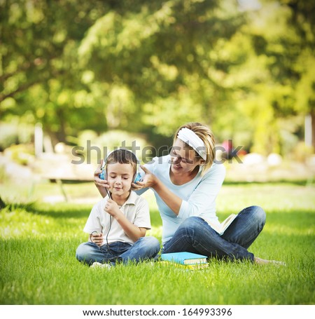 Mother and child listening music in the park - stock photo
