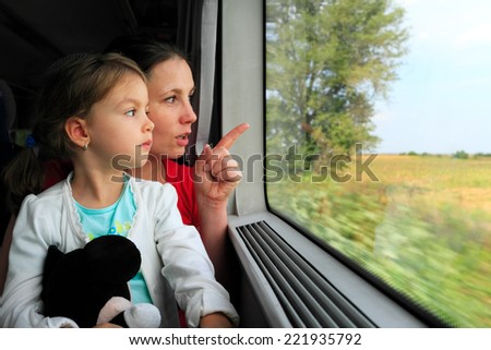 Mother and child looking on the train window - stock photo