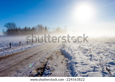 Mother and child on foggy snow road near farm