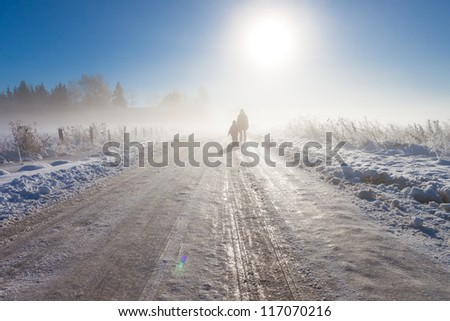 Mother and child on foggy snow road near farm and fence