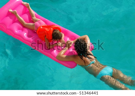 Mother and child on mattress in pool - stock photo