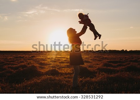 Mother and child on sunset - stock photo
