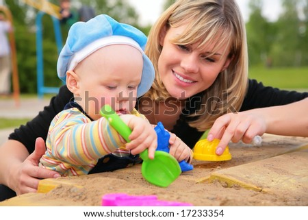 mother and child  play in sandbox - stock photo