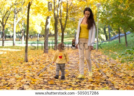 Mother and child playing with leaves in autumn park