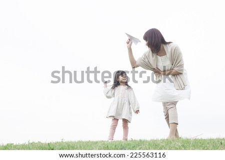 Mother and child playing with the paper plane - stock photo