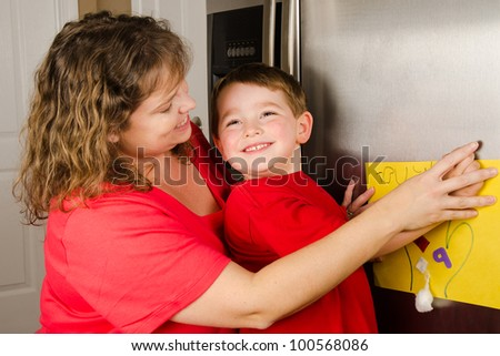 Mother and child putting up boy's art on family refrigerator at home - stock photo