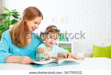 mother and child reading a book together at home - stock photo