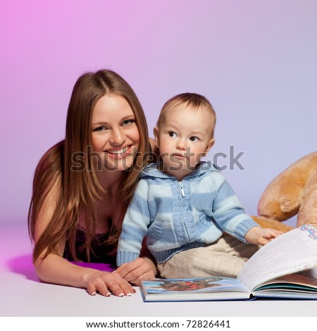 Mother and child reading picture book. studio shot. - stock photo