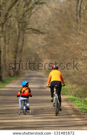 Mother and child riding bikes together during springtime - stock photo