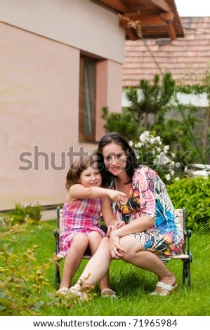 Mother and child siting on bench in garden - girl showing with hand