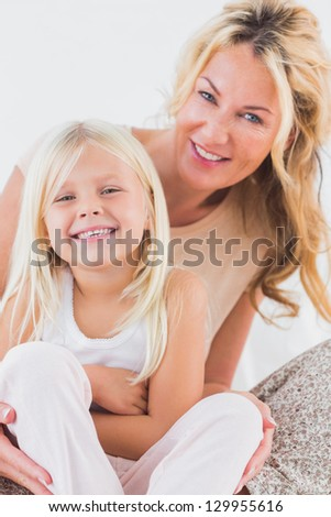 Mother and child sitting on a bed looking at camera - stock photo