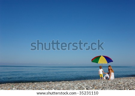 Mother and child under umbrella on seaside - stock photo