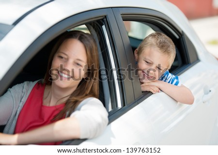 Mother and child waiting for something inside the car - stock photo
