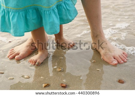 Mother and child walking on a sandy beach - stock photo