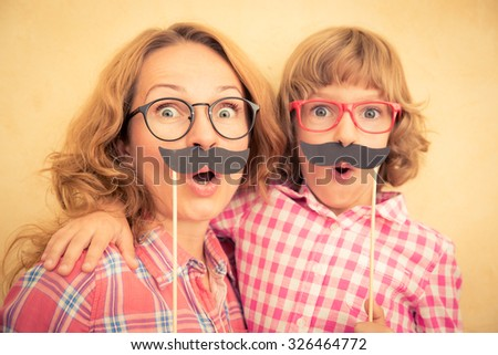 Mother and child with fake mustache. Happy family playing in home  - stock photo