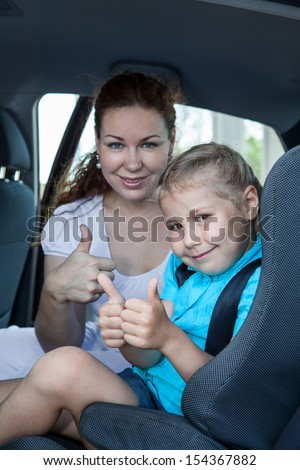 Mother and child with thumb up gesture in car safety seat - stock photo