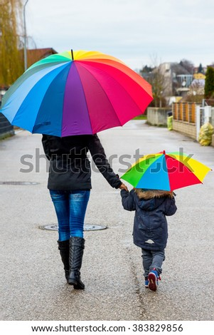 mother and child with umbrella - stock photo