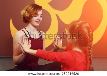 Mother and child yoga practice on the background of the Indian symbol of OM. Beautiful young mother with little daughter doing yoga. Sports family - stock photo